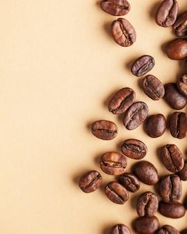 Um punhado de grãos de café arábica sobre um fundo marrom claro. foto vertical com lugar para texto para cafés, protetores de tela, torrefadoras e cafeteiras.