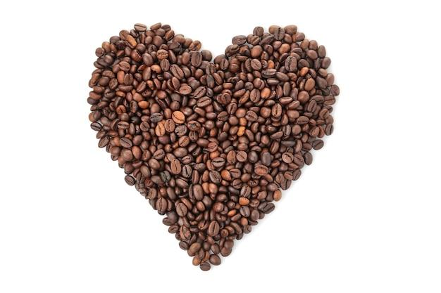 Um punhado de grãos de café em forma de coração em um fundo branco e isolado. fechar-se. vista de cima. grãos de café torrados.