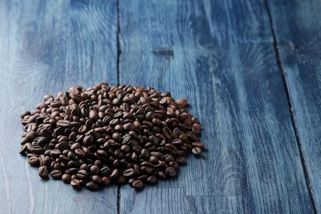 Um punhado de grãos de café torrados em uma mesa de madeira azul. espaço para texto