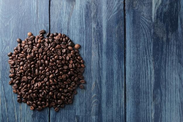 Um punhado de grãos de café torrados em uma mesa de madeira azul. lugar para texto. vista de cima