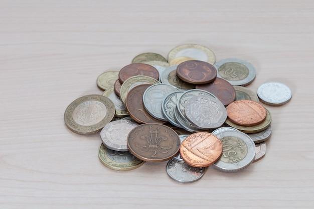 Um punhado de moedas de diferentes países, cor, dignidade e tamanho estão espalhadas sobre a mesa.