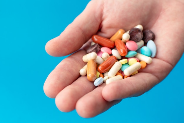 Um punhado de pílulas coloridas na palma da mão.