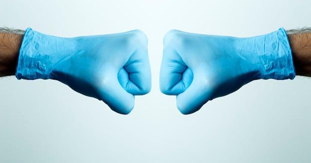 Um punho em uma luva médica. mão do médico em uma luva médica azul sobre um fundo claro.