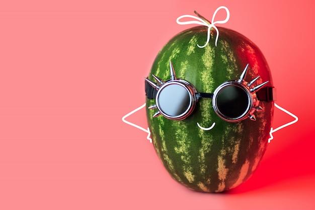 Um punk de melancia em balancins em fundo rosa