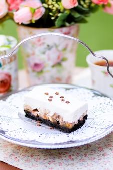 Um quadrado de torta de banoffee com creme na parte superior com flores e fundo de jardim