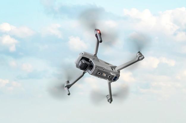 Um quadricóptero voador está sobre fundo azul.