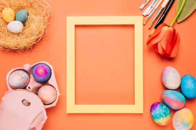 Um quadro amarelo vazio da beira cercado com ovos da páscoa; ninho; pincéis de tulipa e tinta em um fundo laranja