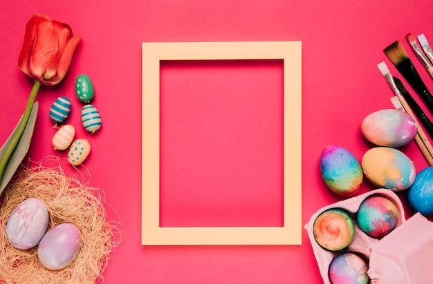 Um quadro amarelo vazio da beira com ovos da páscoa coloridos; pincéis de pintura; tulipa no pano de fundo rosa