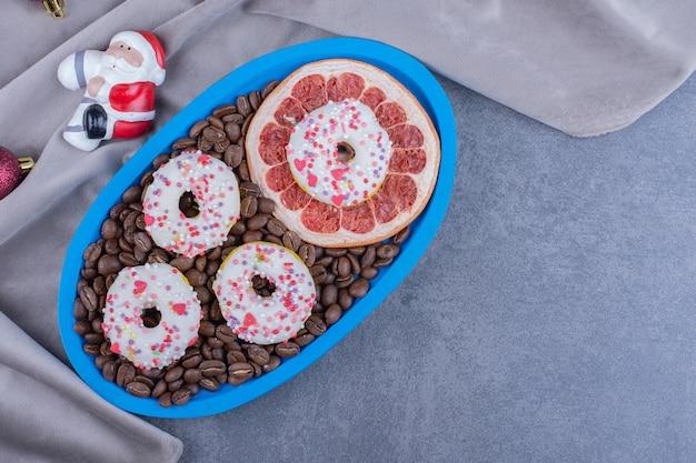 Um quadro azul cheio de grãos de café e donuts