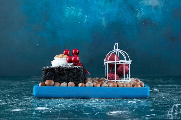 Um quadro azul com um pedaço de bolo de chocolate e nozes de macadâmia. foto de alta qualidade