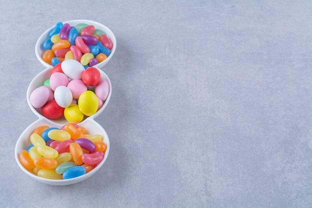 Um quadro branco cheio de doces de feijão coloridos na superfície cinza