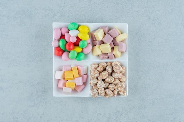 Um quadro branco com marshmallows e doces coloridos na superfície branca
