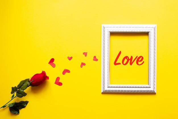 Um quadro branco e corações em um fundo amarelo e uma rosa vermelha. plano de fundo dia dos namorados.