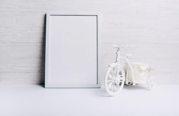 Um quadro branco vazio perto da bicicleta na mesa branca contra a parede de madeira