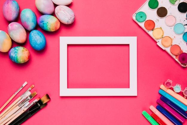 Um quadro de borda branca vazia com ovos de páscoa; pincéis de pintura; canetas de ponta de feltro e caixa de pintura de cor de água no fundo rosa