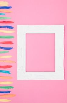 Um quadro de borda branca vazia perto da pena colorida contra fundo rosa