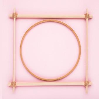 Um quadro de madeira circular e quadrado vazio no pano de fundo rosa