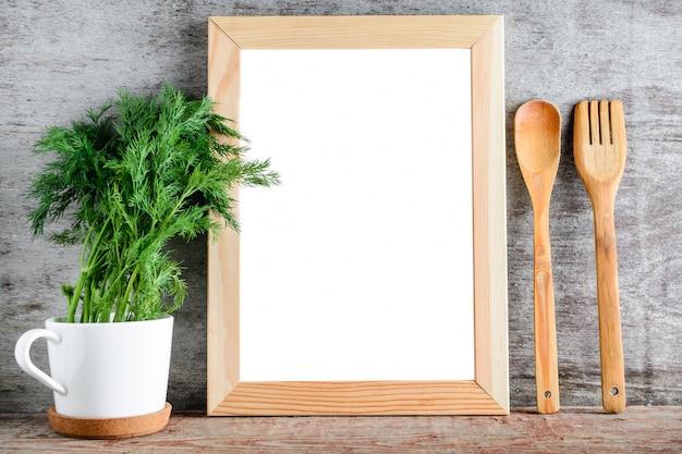 Um quadro de madeira vazio e acessórios da cozinha em uma parede cinzenta.