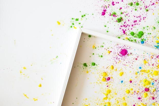 Um quadro de madeira vazio em fundos brancos com pó de cor holi