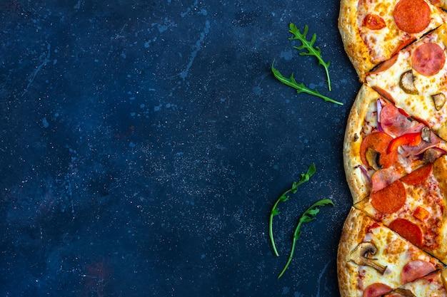 Um quadro de pizza de pepperoni fatias com salame, cogumelos, presunto e queijo em um fundo escuro. almoço ou jantar tradicional italiano. conceito de fast-food e comida de rua. configuração plana