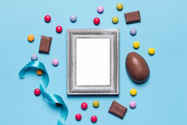 Um quadro de prata branco vazio vazio cercado com ovo da páscoa; doces de gema e pedaços de chocolate no pano de fundo azul