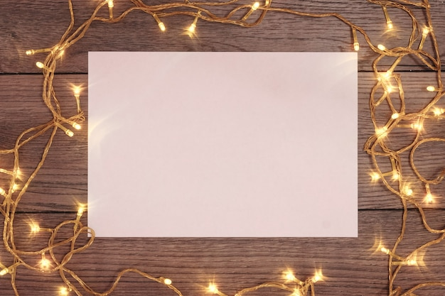Um quadro de ramos de pinheiro e decorações de natal e folha a4 de papel branco sobre uma mesa de madeira. feriados de natal. copyspace. vista de cima.