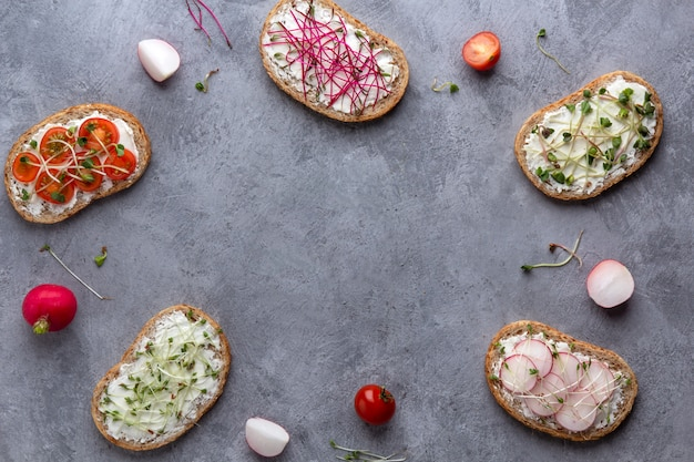 Um quadro de sanduíches com legumes e microgreens em um fundo cinza de concreto