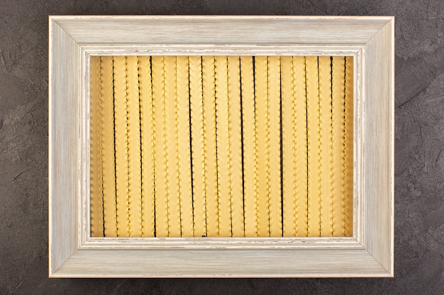 Um quadro de vista frontal com macarrão quadrado cinza moldura moldada isolado no fundo escuro macarrão de comida de foto