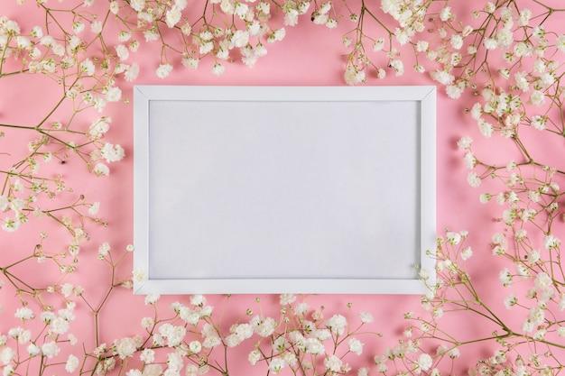 Um quadro em branco branco vazio cercado com flores de respiração do bebê branco contra um fundo rosa