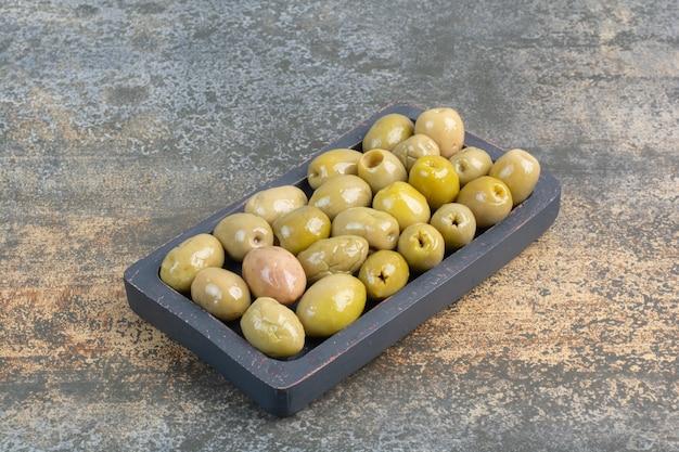 Um quadro escuro de azeitonas salgadas deliciosas no fundo de mármore