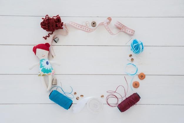 Um quadro feito com boneco de pano; dedal; lã; fita métrica; botão; carretel de fita e fio na mesa de madeira