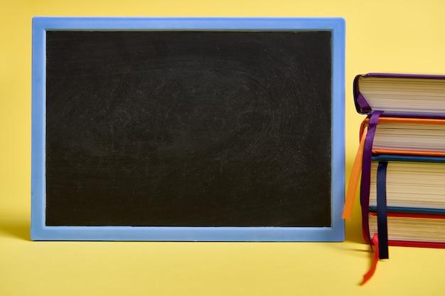Um quadro-negro em branco e livros multicoloridos sobre fundo amarelo de superfície com espaço de cópia para o texto. conceito do dia do professor, conhecimento, literatura, leitura, erudição