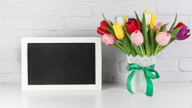 Um quadro preto vazio com vaso de tulipas na mesa contra a parede de tijolos brancos