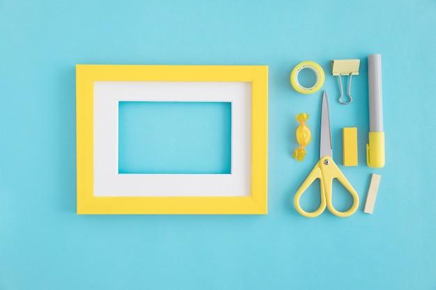 Um quadro vazio com borda branca e amarela e artigos de papelaria no fundo azul
