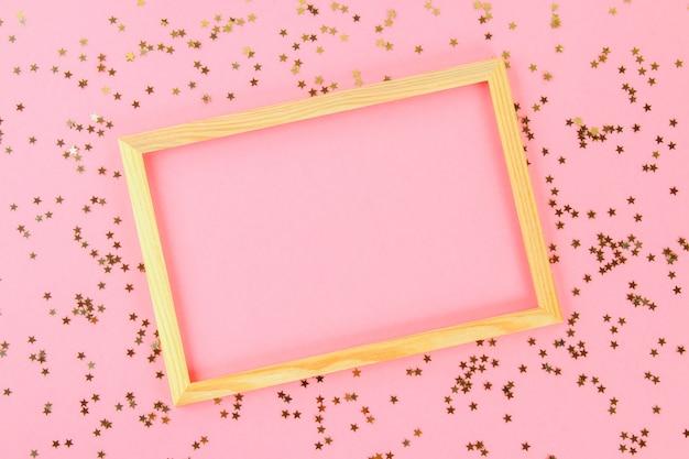 Um quadro vazio de madeira em um fundo pastel cercado por estrelas e por bolas decorativas brilhantes.