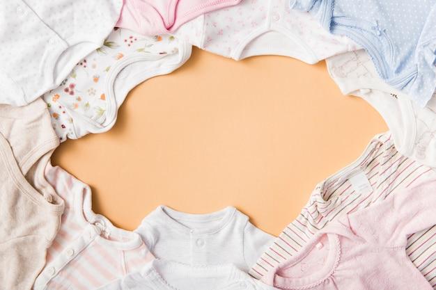 Um quadro vazio feito com roupas de bebê em um pano de fundo laranja