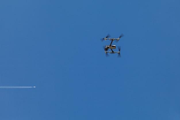 Um quadrocopter suspenso no ar contra um céu azul e um avião voando