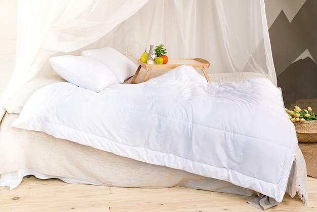 Um quarto aconchegante em tons pastel com piso de madeira, uma grande cama de dossel, bandeja com fr