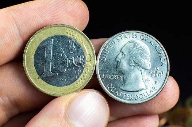 Um quarto de dólar e um euro fecham a foto. moedas macro.