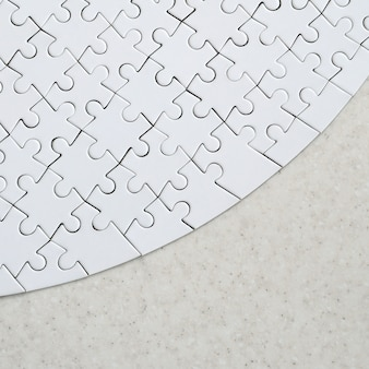 Um quebra-cabeça branco na forma completa está em uma superfície de pedra tratada. imagem texturizada com espaço para texto