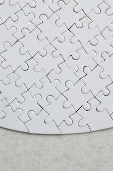 Um quebra-cabeça branco na forma completa está em uma superfície de pedra tratada