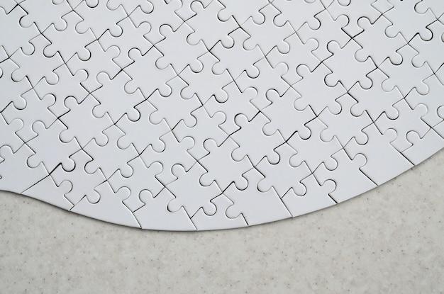 Um quebra-cabeça branco na forma completa está em uma superfície de pedra tratada.