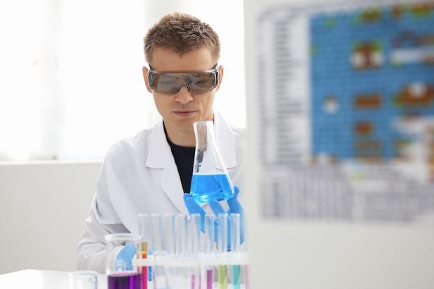 Um químico do sexo masculino segura um tubo de ensaio de vidro na mão e transborda uma solução líquida