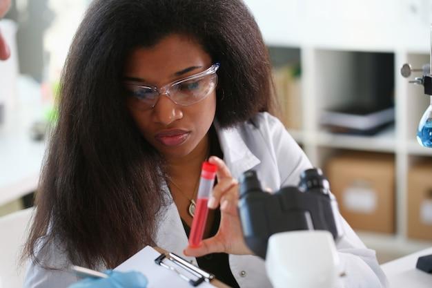 Um químico masculino detém o tubo de ensaio de vidro