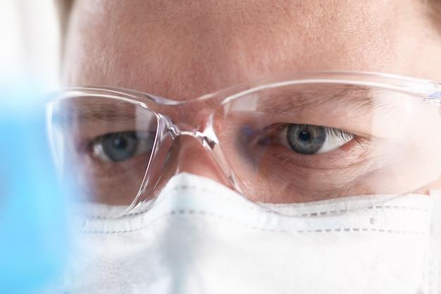 Um químico masculino segura o tubo de ensaio de vidro na mão