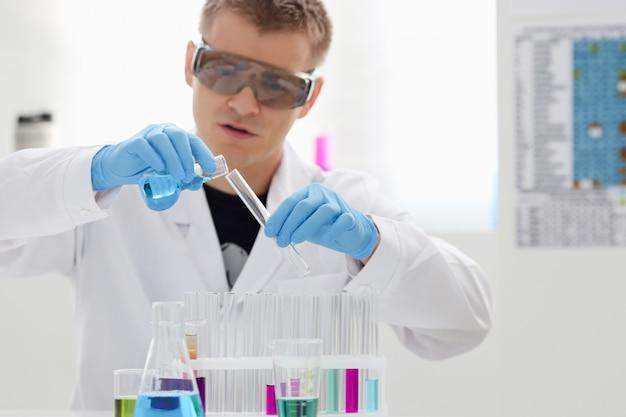 Um químico masculino segura o tubo de ensaio de vidro