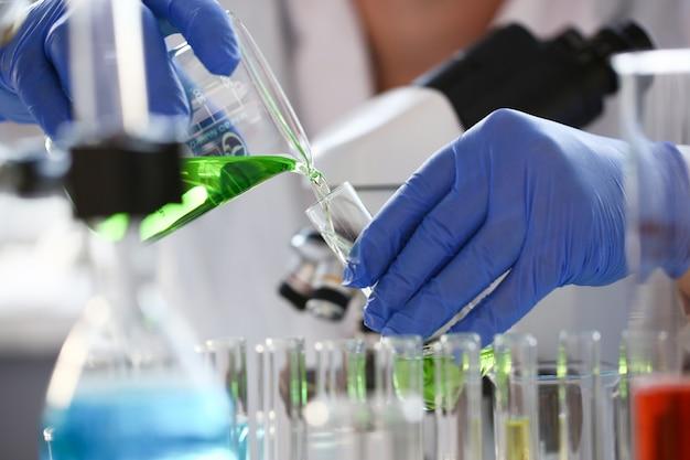 Um químico masculino tem tubo de ensaio de vidro na mão