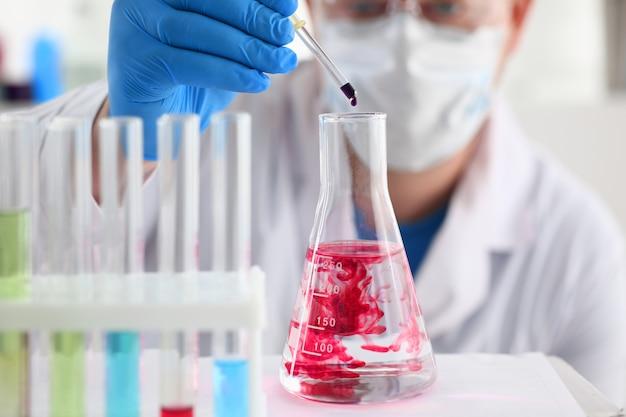 Um químico masculino tem um tubo de ensaio de vidro na mão, transborda um líquido