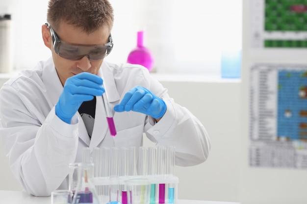 Um químico masculino tem um tubo de ensaio de vidro na mão, transborda uma solução líquida