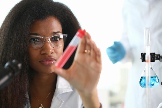 Um químico segurando um tubo de ensaio de vidro